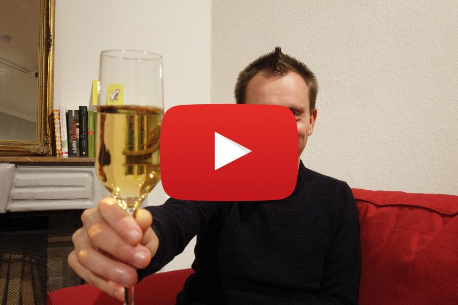 Ralf Wiechers sitz auf Sofa vor einem Kamin und hält ein Sektglas in die Kamera - verdeckt von einem Play-Button